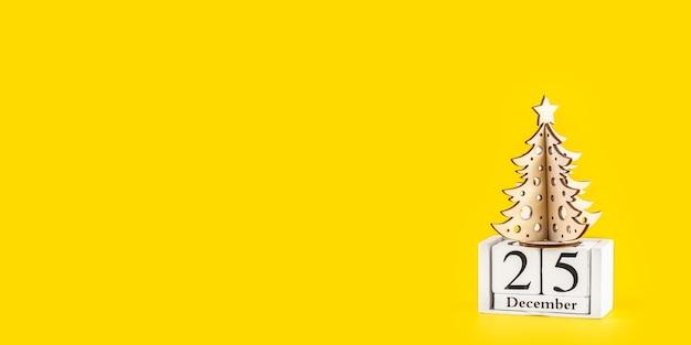 Minimalistische kerstboom op gele pastel trendy achtergrond. prettige kerstdagen en gelukkig nieuwjaar wenskaart met kopie ruimte. winter vakantie concept. lange brede banner. Premium Foto