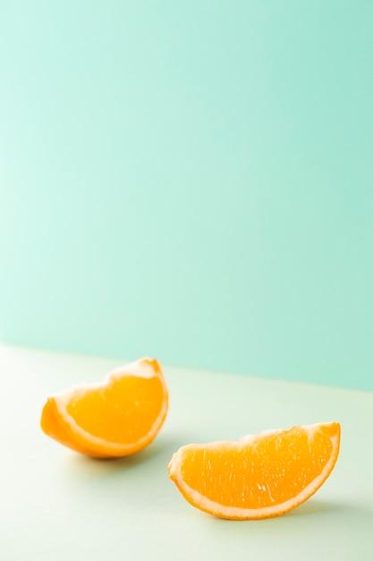 Minimalistische plakjes sinaasappel op blauwe achtergrond Gratis Foto