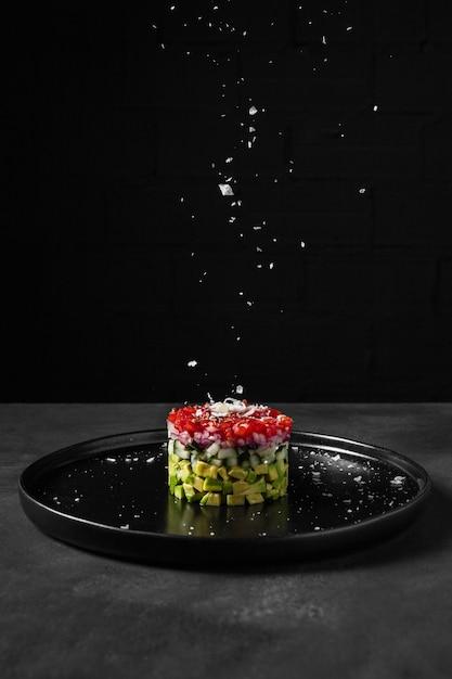 Minimalistische salade in een ronde vorm en zout Gratis Foto