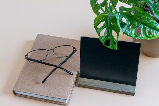Minimalistische werkplek met tijddagboek, bril met ogen en zwarte blanco. mockup-foto met ruimte voor uw tekst. Premium Foto