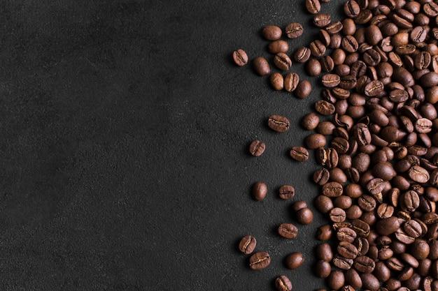 Minimalistische zwarte achtergrond en opstelling van koffiebonen Premium Foto