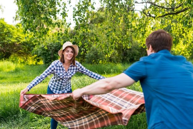 Minnaars die picknickdeken van aard zetten Gratis Foto