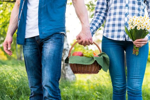 Minnaars die picknickmand op weide houden Gratis Foto