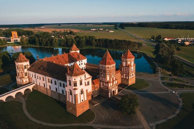 Mir kasteel met torenspitsen in de buurt van het bovenaanzicht van het meer in wit-rusland in de buurt van de stad mir. Premium Foto