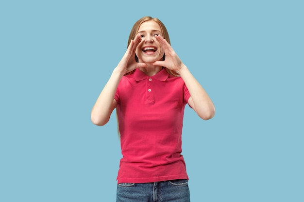 Mis niet. het jonge toevallige vrouw schreeuwen. roepen. huilende emotionele vrouw die op blauwe studioachtergrond gilt. vrouwelijke halve lengte portret. menselijke emoties, gezichtsuitdrukking concept. trendy kleuren Gratis Foto