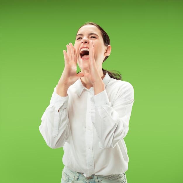 Mis niet. het jonge toevallige vrouw schreeuwen. roepen. huilende emotionele vrouw die op groene studioachtergrond gilt. vrouwelijke halve lengte portret. menselijke emoties, gezichtsuitdrukking concept. trendy kleuren Gratis Foto