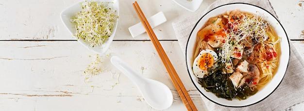 Miso noedels met kimchi van kool, zeewier, ei, champignons en kaas tofu in kom op witte houten tafel Premium Foto