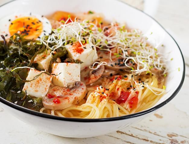 Miso ramen aziatische noedels met koolkimchi, zeewier, ei, paddestoelen en kaastofu in kom op witte houten lijst. Premium Foto