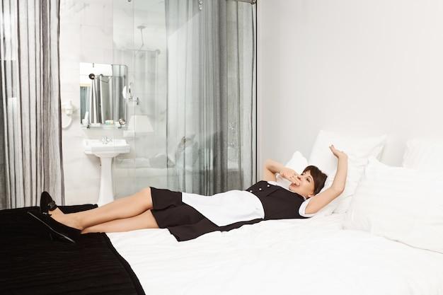 Misschien moet ik een dutje doen voordat klanten komen. schot van vermoeide vrouw in meid uniform liggend op bed en geeuwen, mond bedekken, uitgeput na het schoonmaken van alle rotzooi klanten achtergelaten in hun hotelkamer Gratis Foto