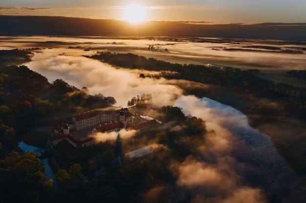Mistige dageraad in nesvizh. uitzicht vanaf de hoogte van het kasteel van nesvizh en het park bij zonsopgang. Premium Foto