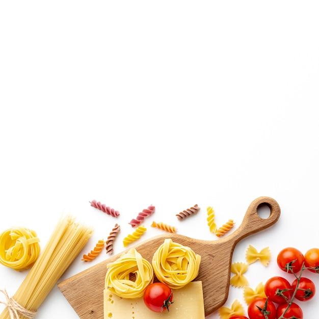 Mix van ongekookte pasta tomaten en harde kaas met kopie ruimte Gratis Foto