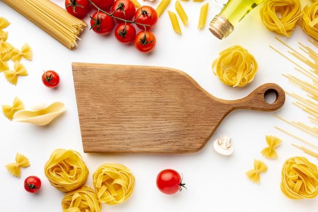 Mix van ongekookte pasta tomaten en snijplank Gratis Foto