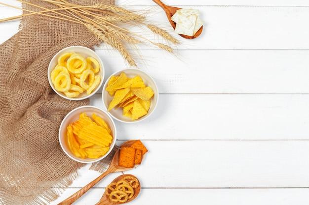 Mix van snacks: pretzels, crackers, chips en nacho's op tafel Premium Foto