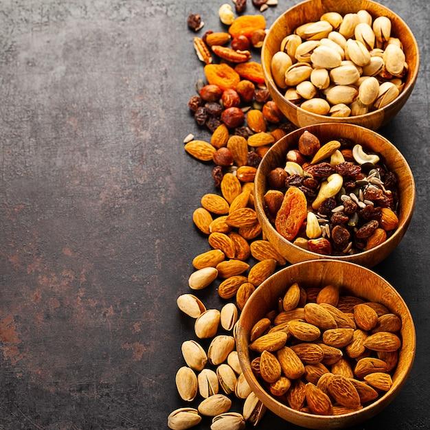 Mix van verschillende noten en gedroogd fruit in houten kommen die zich op rustiek bevinden Premium Foto