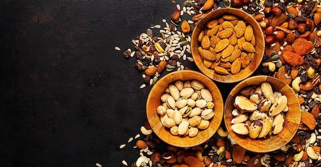 Mix van verschillende noten en gedroogde vruchten in houten kom staande op rustiek Premium Foto