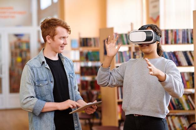 Mixed-race student met vr-headset en haar klasgenoot met touchpad bespreken punten van presentatie in bibliotheek Premium Foto
