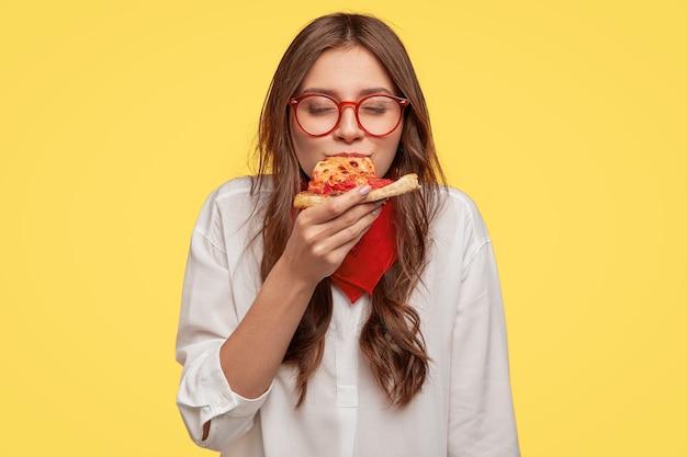 Mmm, zo lekker! donkerharige mooie vrouw eet plakje italiaanse pizza, houdt de ogen gesloten van plezier, geniet van een lekkere smaak, draagt een bril en shirt, geïsoleerd over gele muur. eten concept Gratis Foto