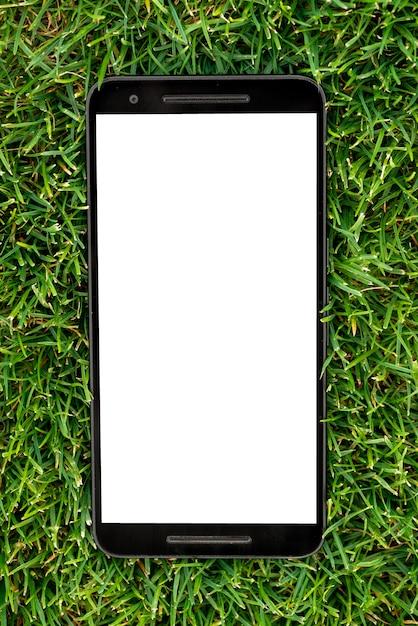 Mobiel slim telefoonmodel met het witte scherm op groene grasachtergrond. Premium Foto