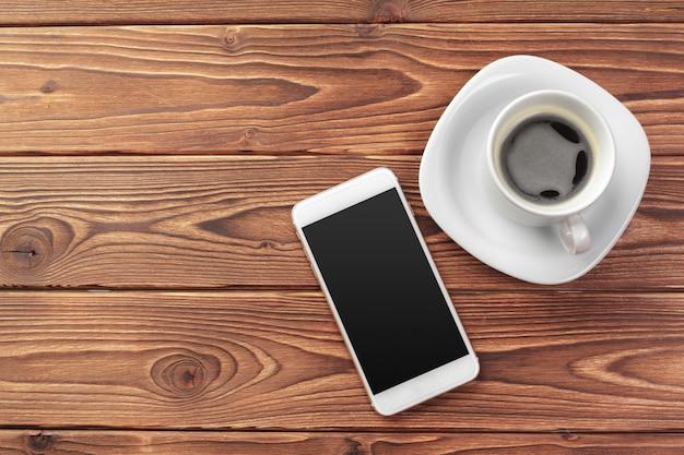 Mobiele slimme telefoon en een kopje koffie op houtstructuur achtergrond Premium Foto
