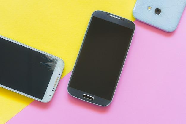 Mobiele smartphones met gebroken glasscherm geïsoleerd op roze en geel. copyspace voor tekst. service, reparatie en technologie concept plat lag. telefoon met gebroken touch Premium Foto