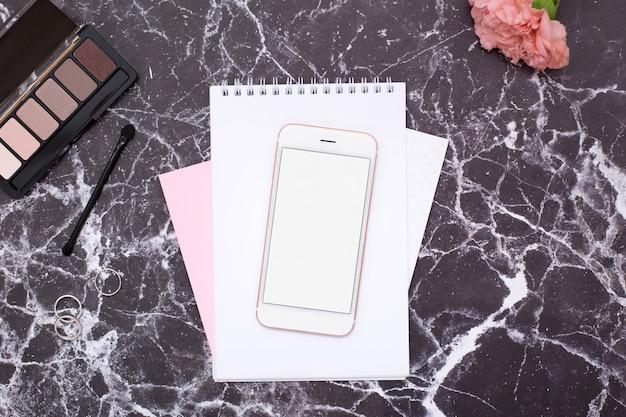 Mobiele telefoon en cosmetica op zwart marmeren tafel Premium Foto