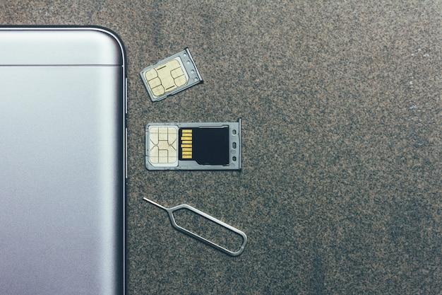 Mobiele telefoon en open slots voor nano-simkaarten, micro sd-schijf en metalen sleutel op grijs met copyspace Premium Foto