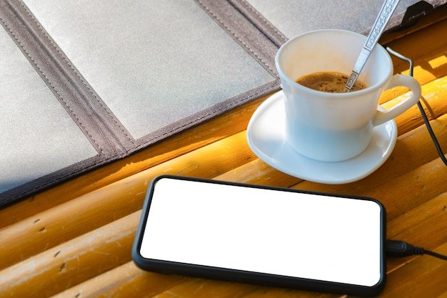 Mobiele telefoon gezet op een bamboetafel in de ochtend met een koffiekop en zonnecellen Premium Foto