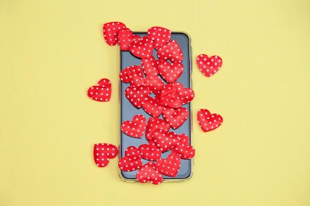 Mobiele telefoon met hartjes, liefde, valentijnskaartdagconcept. Premium Foto