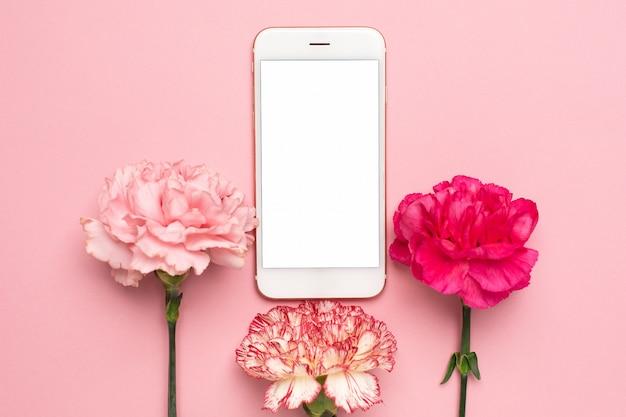 Mobiele telefoon met roze anjerbloem op roze achtergrond Premium Foto