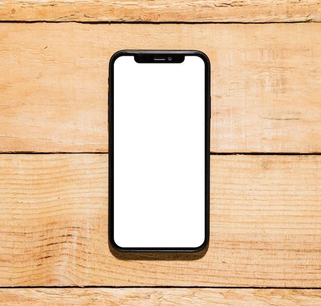 Mobiele telefoon met wit scherm op houten bureau Gratis Foto
