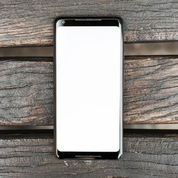 Mobiele telefoon met wit scherm op houten structuur plank Gratis Foto