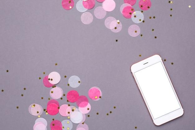 Mobiele telefoon mock up en roze confetti met gouden sterren op grijs Premium Foto