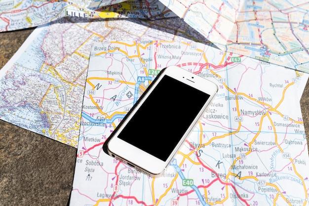 Mobiele telefoon op toeristische polen kaarten Gratis Foto