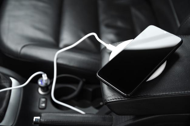 Mobiele telefoon, smartphone laadbatterij, draadloos opladen in de autostekker close-up Premium Foto
