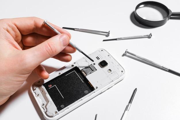 Mobiele telefoonreparatie, handenclose-up Premium Foto