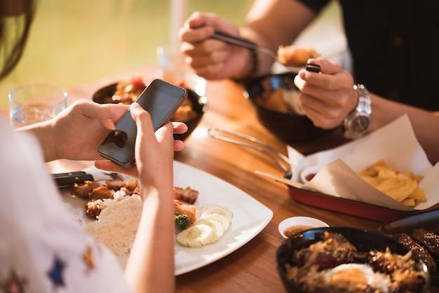 Mobiele vrouw terwijl dineren met vrienden in restaurant Premium Foto
