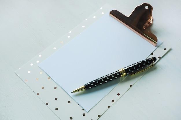 Mock up klembord en zwart witte polka dot pen op witte tafel. Premium Foto