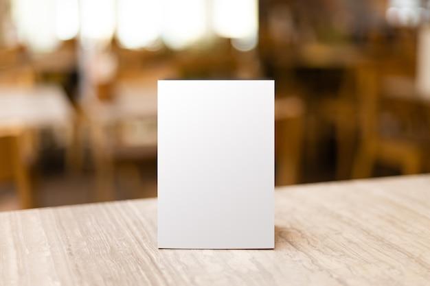Mock-up label het lege menuframe in het bar-restaurant. stand voor boekje met wit vel papier acryl tentkaart Premium Foto