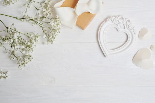 Mock up samenstelling van witte bloemen, rustieke stijl, hartenliefde en een geschenk. valentijn kaart Premium Foto
