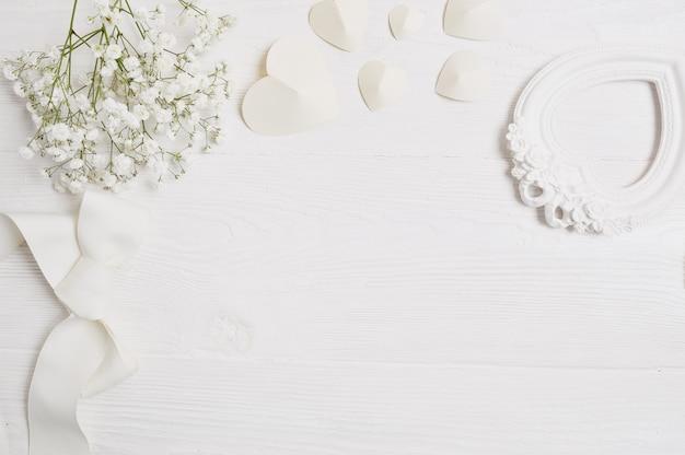 Mockup achtergrond met bloemen en papier harten voor wenskaart st. valentijnsdag Premium Foto