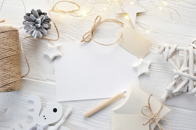 Mockup christmas wenskaart bovenaanzicht, flatlay op een witte houten achtergrond Premium Foto