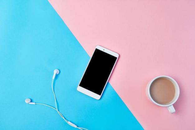 Mockup flat lag compositie met smartphone, koptelefoon en kopje koffie op een blauwe en roze achtergrond. Premium Foto