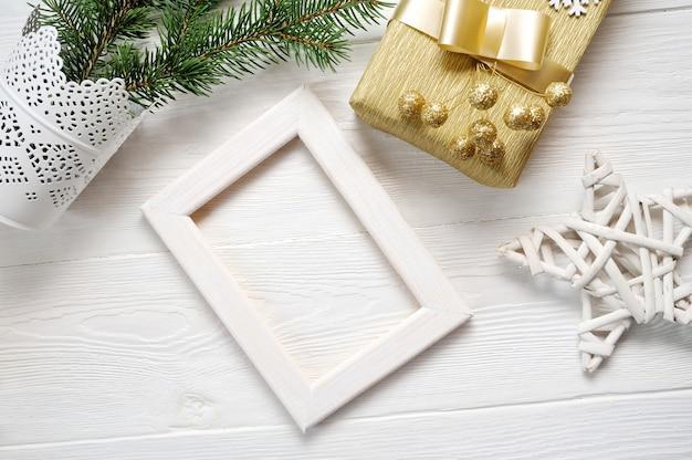 Mockup kerst wit frame met boom en gouden lint en een cadeau Premium Foto