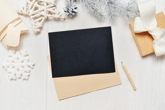 Mockup kerst zwarte wenskaart brief in envelop met witte boom Premium Foto
