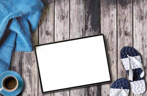 Mockup leeg scherm tablet, handdoek, kopje koffie op houten tafel Premium Foto