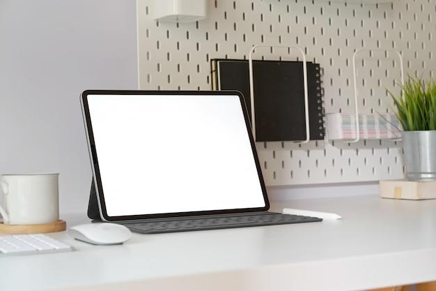 Mockup-tablet met slim toetsenbord op minimale werkruimtetafel. Premium Foto