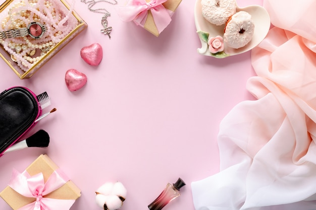 Mode blogger werkruimte met laptop en vrouwelijke accessoire, cosmetische producten op roze tafel. Premium Foto