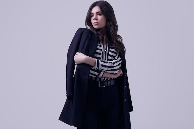 Mode brunette vrouw draagt een gestreepte blouse en een zwarte jas Premium Foto