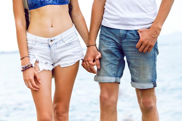 Mode buiten portret van jonge man met hand van haar vriendin, jonge hipster verliefde paar genieten van reizen in de zomer samen, poseren aan zee. Gratis Foto
