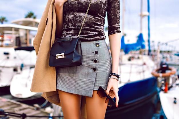 Mode details van vrouw die zich voordeed op straat in de buurt van luxe jachthaven met jachten`` sexy rok, beige jas dragen, luxe lederen tas en zonnebril, lente herfst middenseizoen tijd houden. Gratis Foto